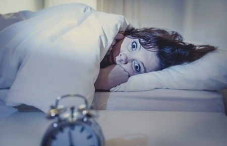 Woman in bed wide eyes and can't fall asleep