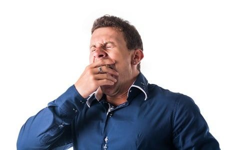 Young man yawning in a blue shirt with a hand over his mouth