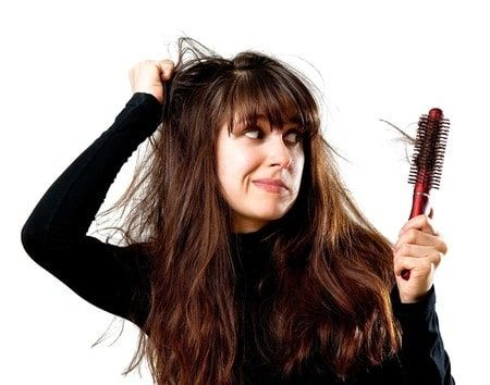 Girl with bad hair looking at a brush with hair stuck in it
