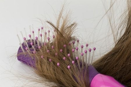 A purple and pink brush with hair in it