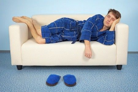 Man in blue robe sleeping on a couch that is too small