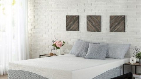 White bed with a purple wave going along the bottom edge of the bed. Placed in a show-room with brick walls