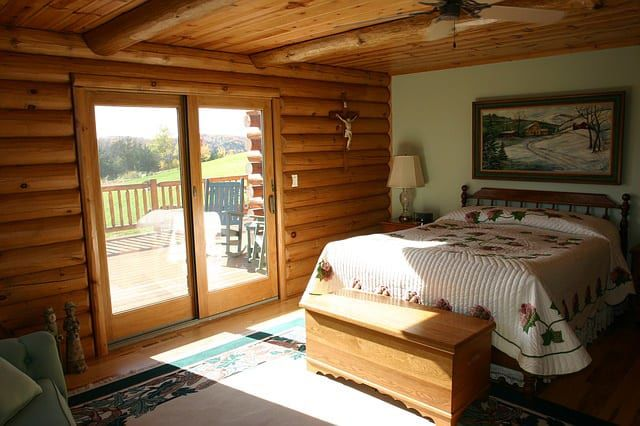 This Beautiful Log Cabin Bedroom Complimented By A Sliding Glass Door Leading Out To Porch Is Ideal For Watching Sunrise If You Have The Space