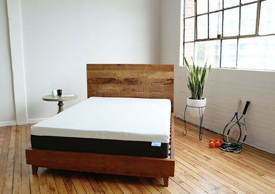 BEar mattress in a well lit room with a wooden bedframe and a plant in the corner