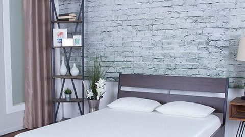 Image of a soft reflex foam based bed in a show-room with a wood bed-frame and gray brick wall behind it