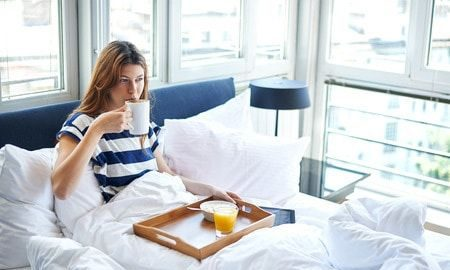 Skip breakfast in bed, a young woman eating breakfast in bed and drinking coffee