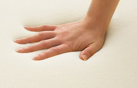 a close up of a hand pressing down on a memory foam mattress