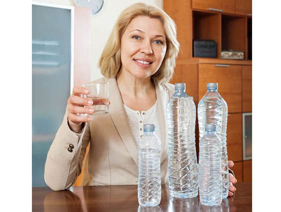 mature woman drinking water at home