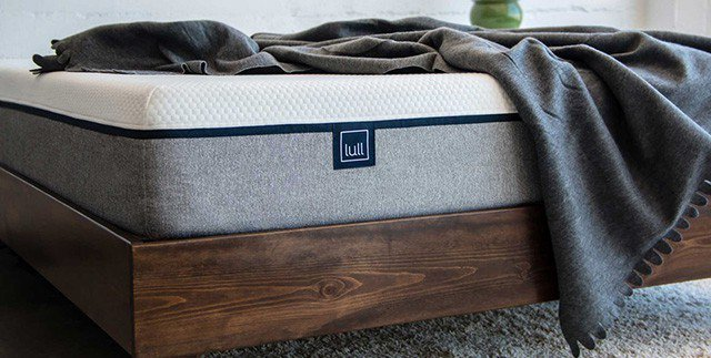 Lull-mattress with a blanked ontop of it and a wood bedframe side shot