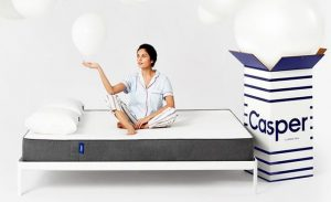 Picture of a woman on a bed sitting on a mattress with casper there