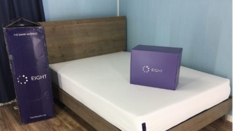 Mars mattress with the app box (blue) place on the bed in a room with blue walls and a wooden bedframe