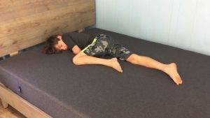 Jess' son lying on the Casper bed with camo shorts and a black shirt
