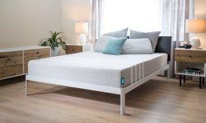 Leesa Mattress image - Leesa gray mattress on a bedframe in a nice lit showroom with tables and drawers