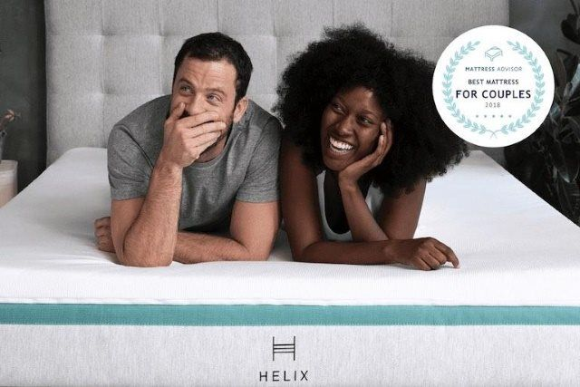A young man and woman laying on Helix' mattress