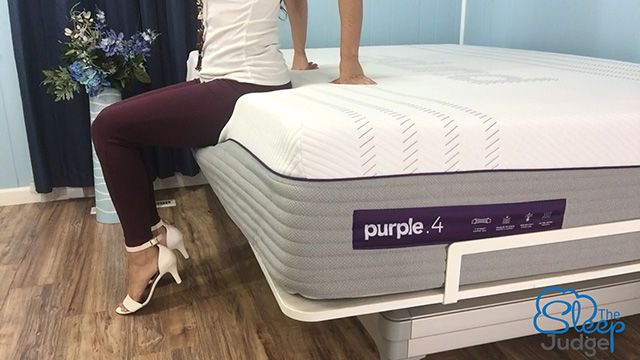 Jess sitting on the edge of a purple mattress testing edge support