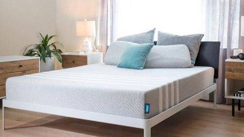 Leesa mattress on a bed frame in a staged well lit room with hardwood