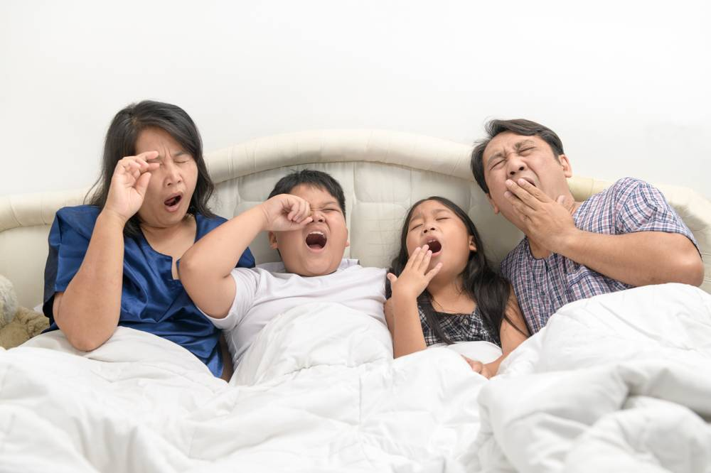 family of four yawning in bed