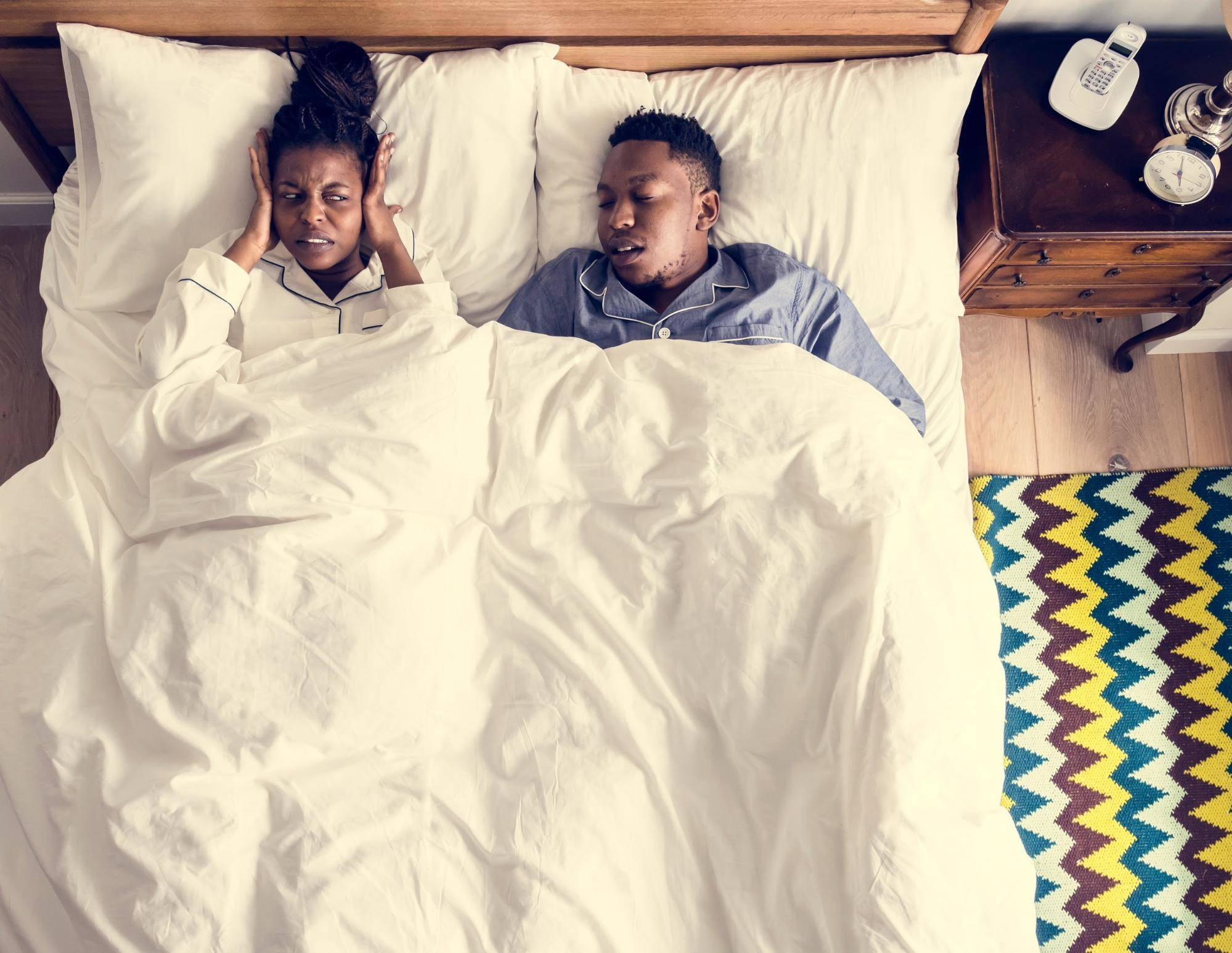 couple sleeping in bed but female cannot sleep