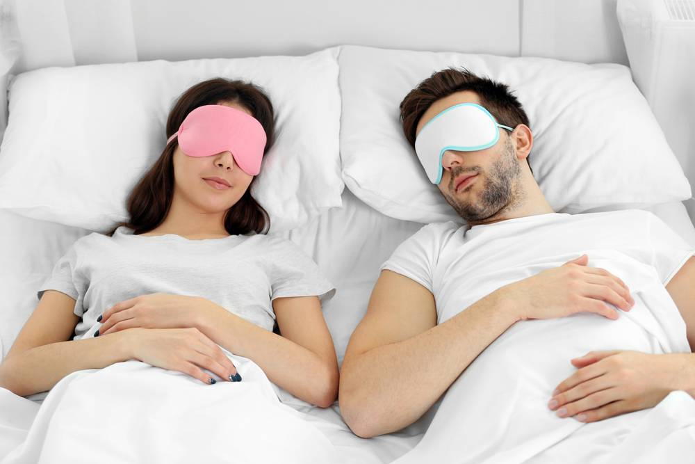 couple laying in bed with sleep masks on