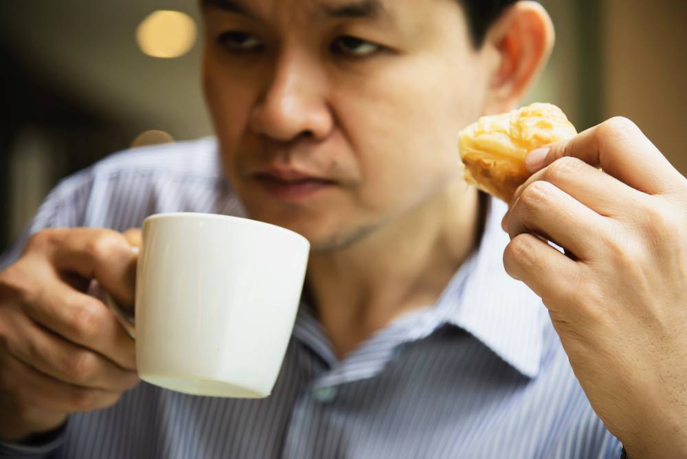 man drinking coffee and snacking on pastry