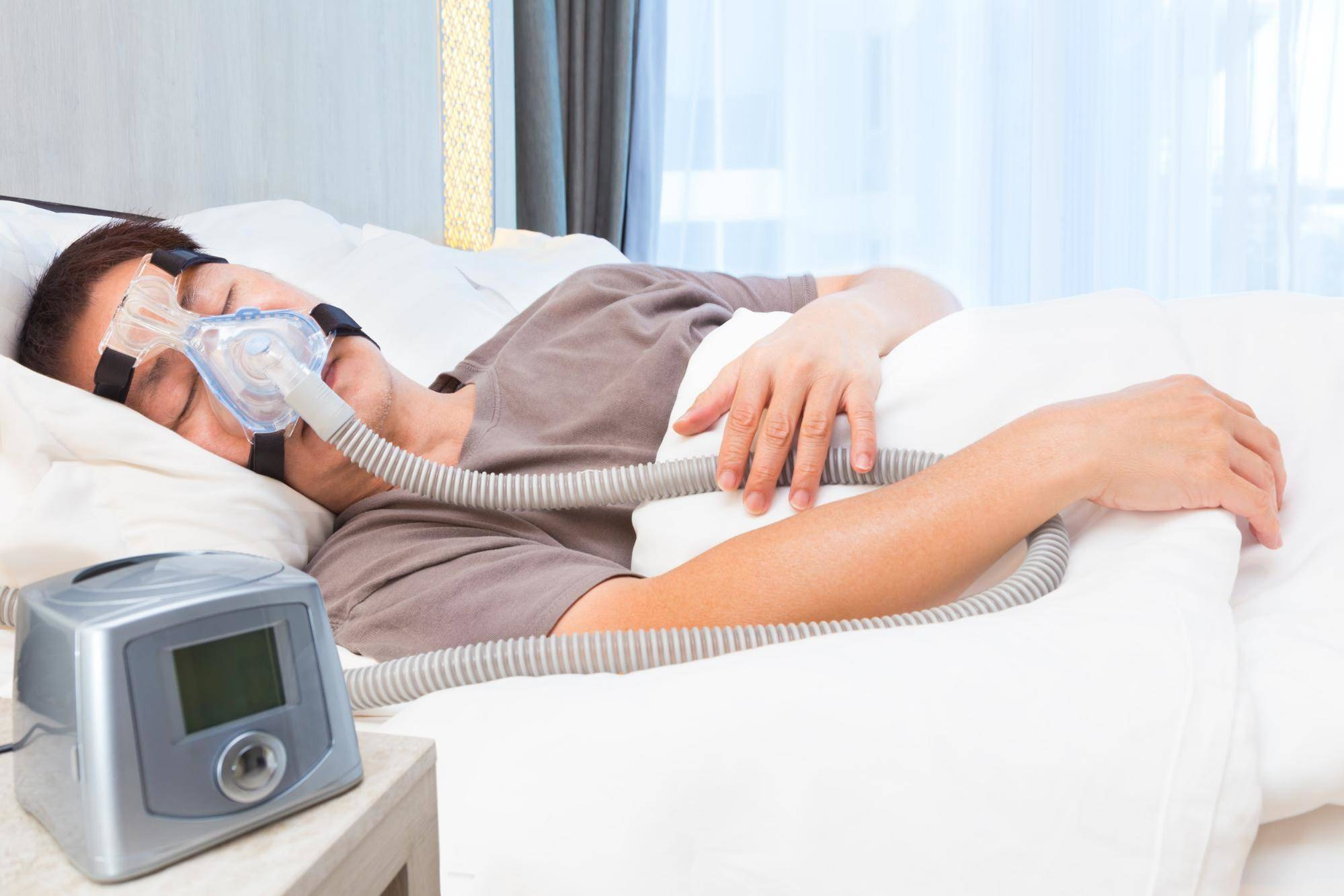 man sleeping in bed with CPAC machine