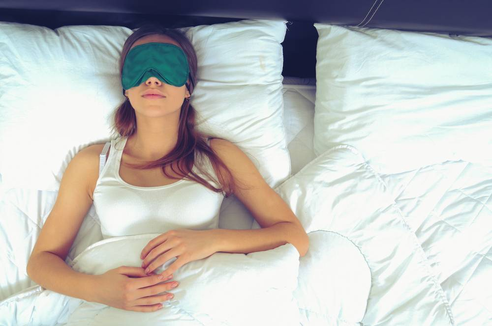 female laying in bed with sleeping mask on