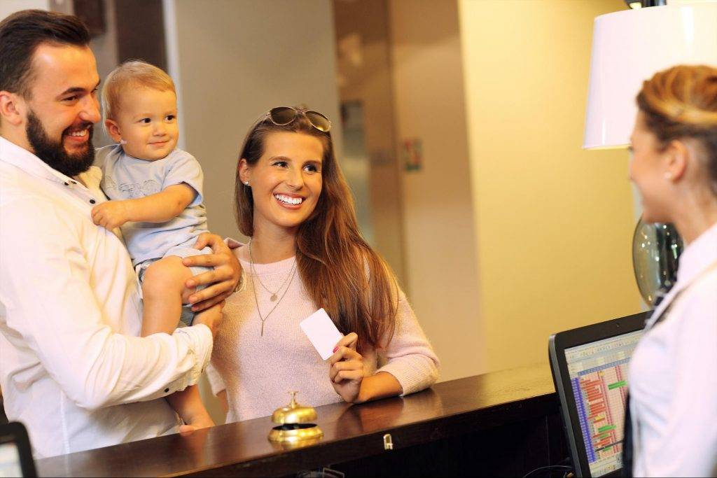 family with baby checking in to hotel