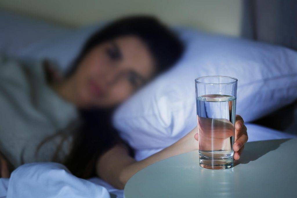 female grabbing a glass of water beside her bed