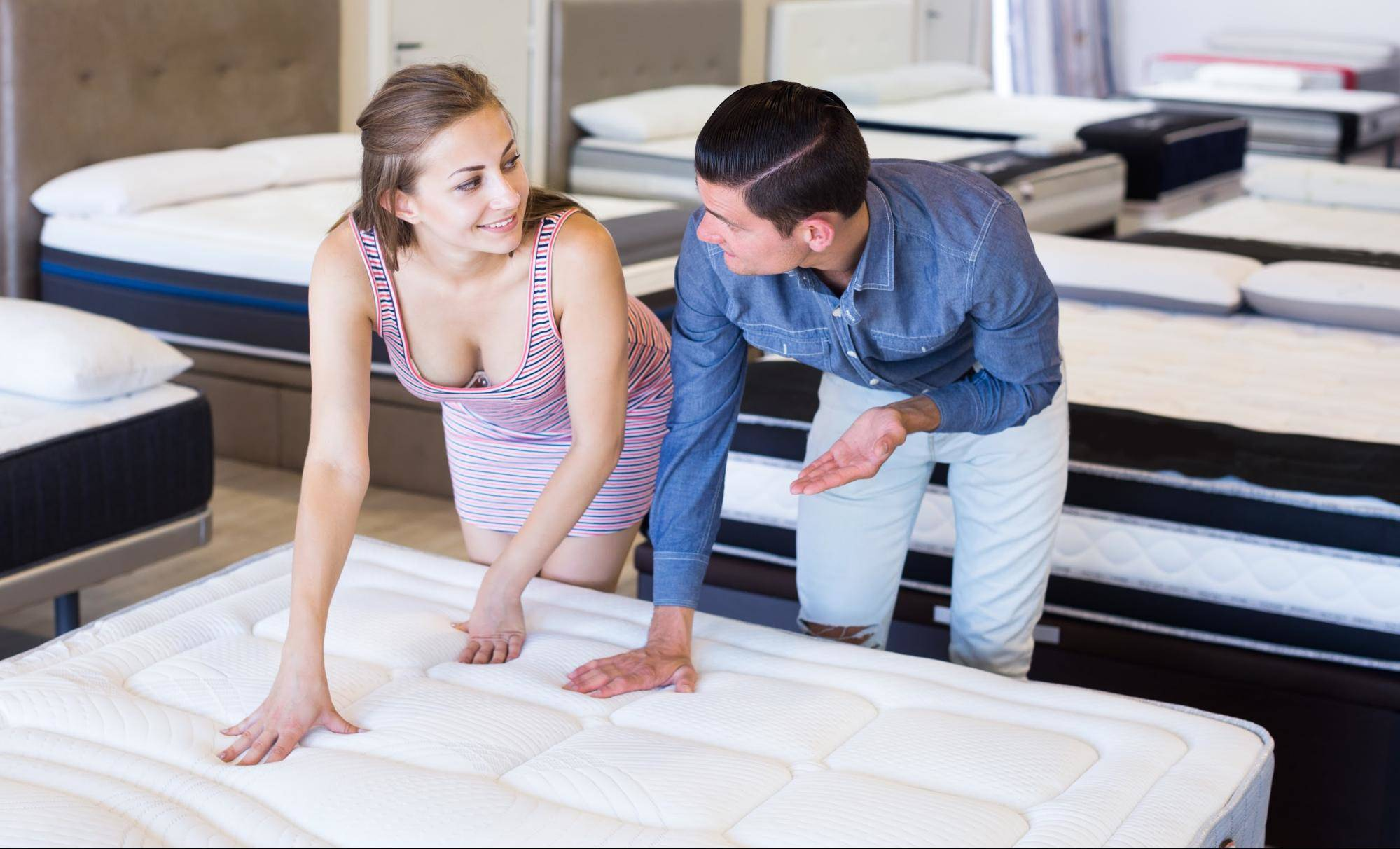 couple testing the firmness of mattress with their hands