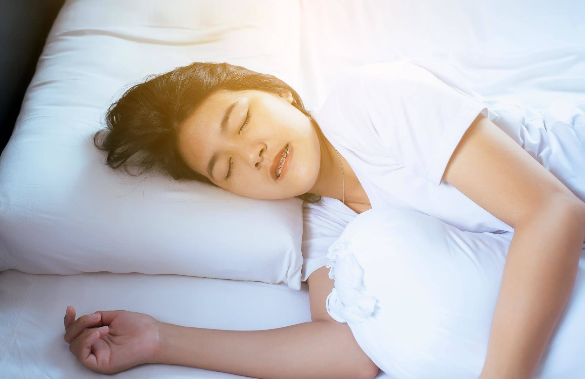 female sleeping on a fluffy pillow with mouthguard