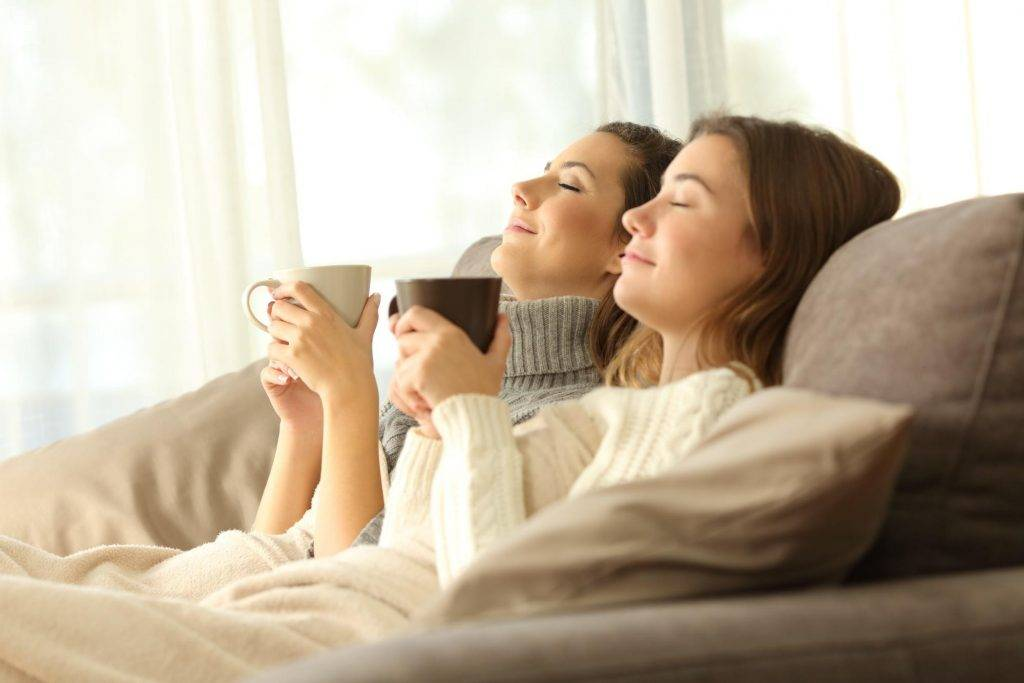 two females drinking from a cup with an electric blanket on top