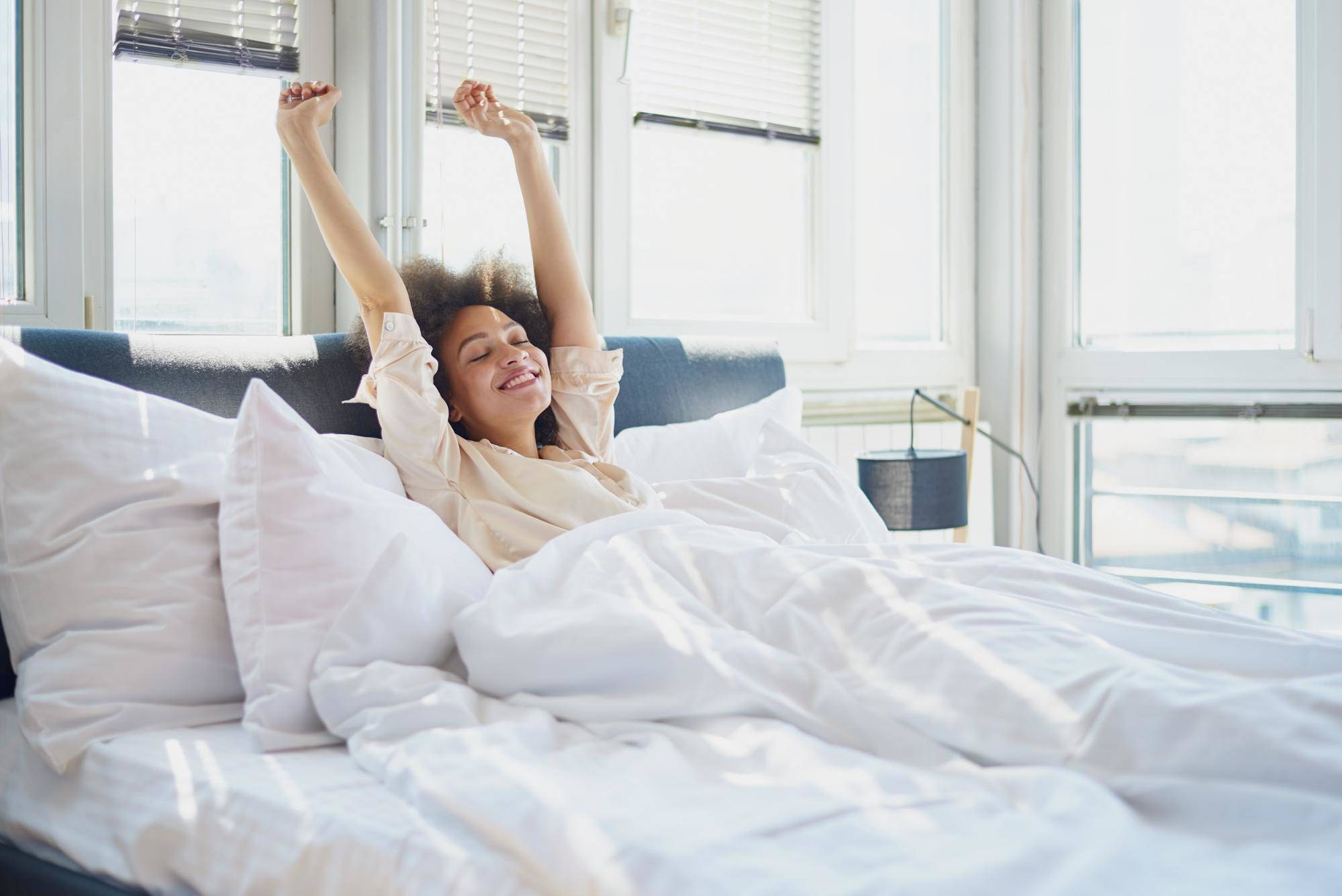 female stretching arms in bed