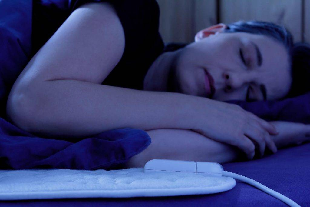 Female sleeping on her side on top of an electric blanket