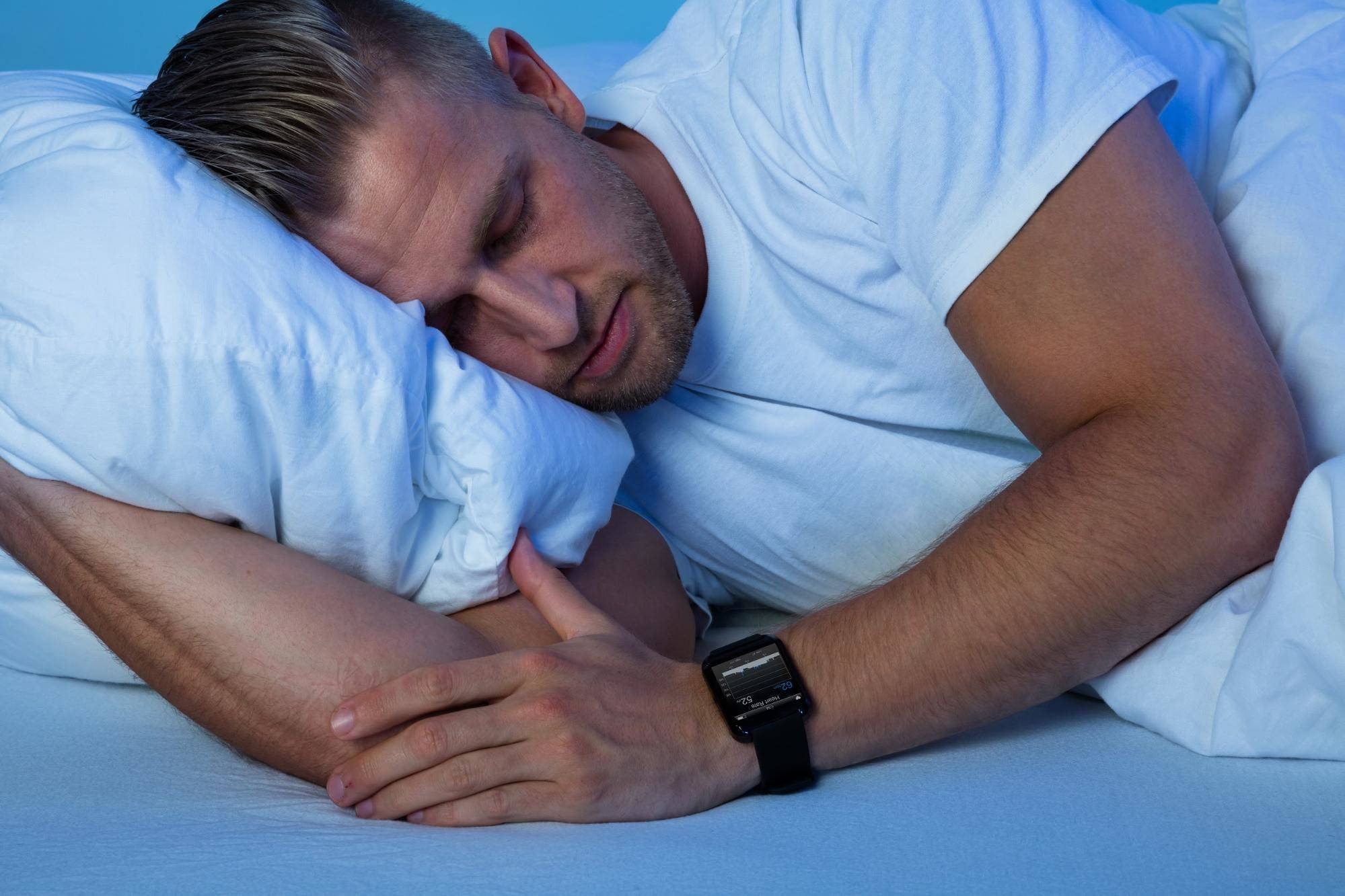 male sleeping on his side with a sleep tracking watch